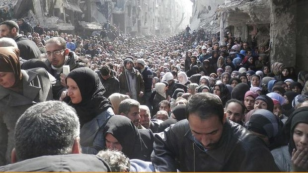 This photograph, taken on January 31 and released by UNRWA on February 26, shows the grim reality for those trapped inside the neighborhood of Damascus' Yarmouk Refugee Camp. Photo courtesy United Nation News Centre via Facebook. Read more: http://www.smh.com.au/world/portrait-of-despair-thousands-queue-for-un-food-parcels-in-yarmouk-damascus-20140227-hve0b.html#ixzz2uX0i9hoh