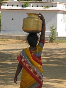 The rich everyday colours of a sari-clad rural women fetching water from the village tank. Water supply is a major problem throughout India and many rural areas lack clean water and supply to the home forcing women to fetch and carry water daily. Most villages lack the resources to invest and ensure a clean supply to each home. Photo by McKay Savage from London, UK [CC-BY-2.0 (http://creativecommons.org/licenses/by/2.0)], via Wikimedia Commons