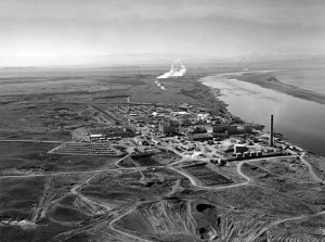 The N Reactor at the Hanford site, along the Columbia River. The twin KE and KW reactors can be seen in the immediate background, with the B Reactor in the distance. Photo by United States Department of Energy (Image N1D0069267.) [Public domain], via Wikimedia Commons