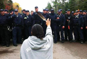 A Mi'kmaq protester raises a symbolic feather in efforts to stop natural gas drilling on what used to be her tribe's land. Canada, October, 2013. Image via Twitter.