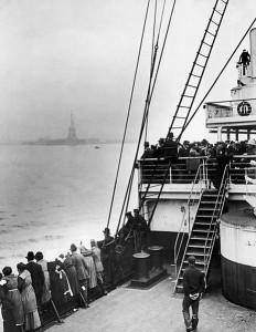 Immigrants on a ship approaching New York City, bound for Ellis Island, with the Statue of Liberty in the background. Image via Wikimedia Commons.