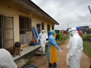 World Health Organization workers gearing up to go into old Ebola isolation ward in Lagos, Nigeria. Photo by CDC Global (WHO in PPE) [CC BY 2.0], via Wikimedia Commons