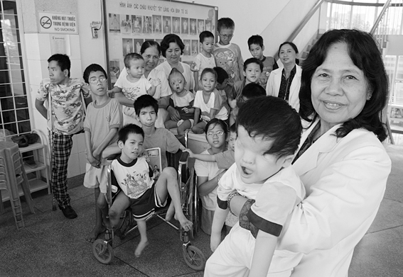 Vietnam. 12/2004. Ho Chi Minh City. Professor Nguyen Thi Ngoc Phuong, at Tu Du Obstetrics and Gynecology Hospital is pictured with a group of handicapped children, most of them victims of Agent Orange.  Photo by Alexis Duclos (Alexis Duclos) [CC-BY-SA-3.0], via Wikimedia Commons