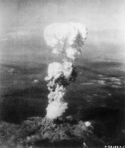 At the time this photo was made, smoke billowed 20,000 feet above Hiroshima while smoke from the burst of the first atomic bomb had spread over 10,000 feet on the target at the base of the rising column. Photo public domain via Wikimedia Commons.