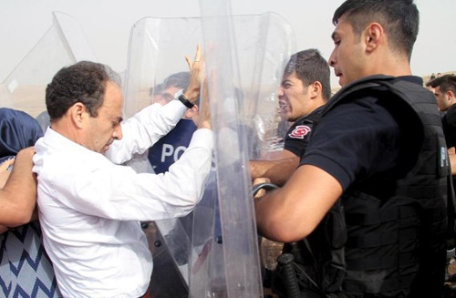 Photo by Sertaç Kayar, showing HDP-deputy Osman Baydemir scuffling with riot police on the road to Cizre.