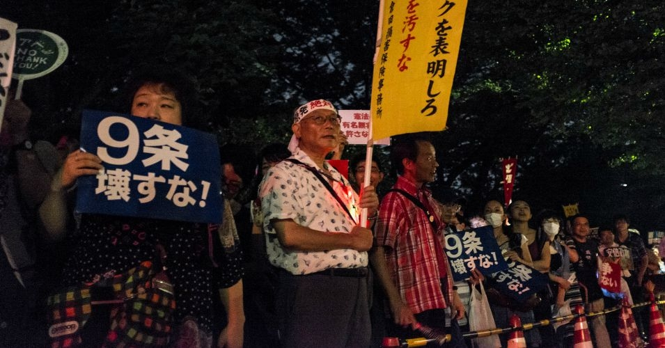 Protesters hold signs against the then-proposed changes to Article 9 of the Japanese constitution. (Photo: Christian c/flickr/cc)
