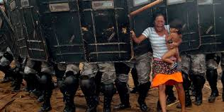 An indigenous woman holds her child while trying to resist the advance of Amazonas state policemen in Manaus who have been sent to evict natives. [2008] Photo via Tumblr
