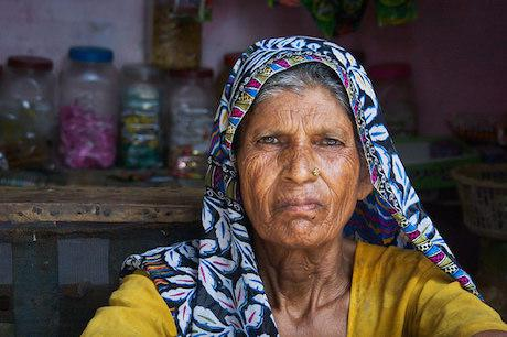 A woman sits in front of her shop near Aligarh. Evonne/Flickr. Some rights reserved.