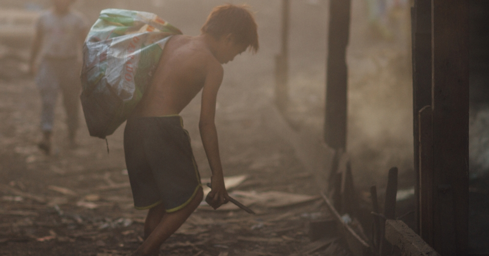 A child scavenges for coal scraps in a slum in Manila. One in four children's deaths around the world are caused by unhealthy environments, the WHO has found. (Photo: Adam Cohn/flickr/cc.)