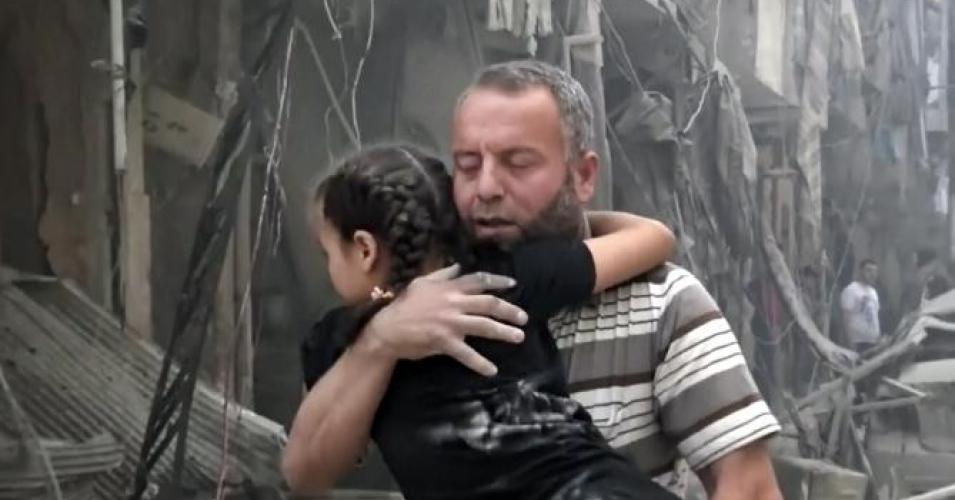 In this image made from video and posted online from Validated UGC, a man carries a child after airstrikes hit Aleppo, Syria, Thursday, April 28, 2016. (Validated UGC via AP video)