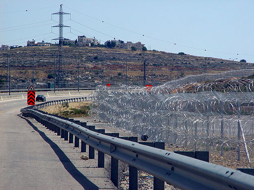 Route 443 near Giv'at Ze'ev Junction, with pyramid-shaped stacks of razor wire forming a section of the Israeli West Bank barrier. Photo: Etan J. Tal (Own work) [CC BY 3.0], via Wikimedia Commons
