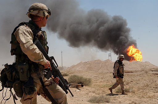 A U.S. soldier stands guard duty near a burning oil well in the Rumaila oil field, 2 April 2003. Photo: US Navy (Public domain) via Wikimedia Commons