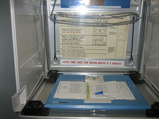 "Voting stand and the notorious ""butterfly ballot"", from Palm Beach County from the disputed 2000 U.S. Presidential election. Photo: Infrogmation (Own work) [CC BY 2.5 ], via Wikimedia Commons"