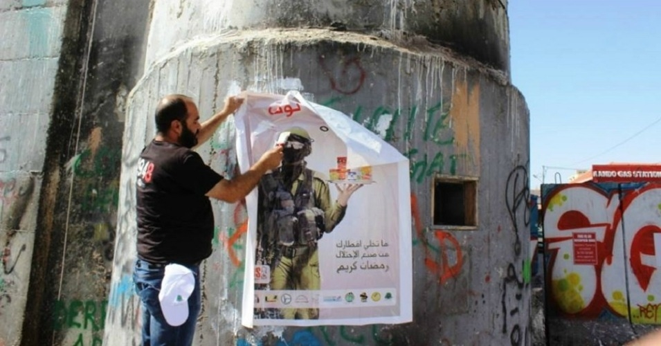 A campaigner in the West Bank puts up a poster in support of a BDS campaign. The Israeli government wants you to report this man. (Photo: Palestinian BDS Movement)