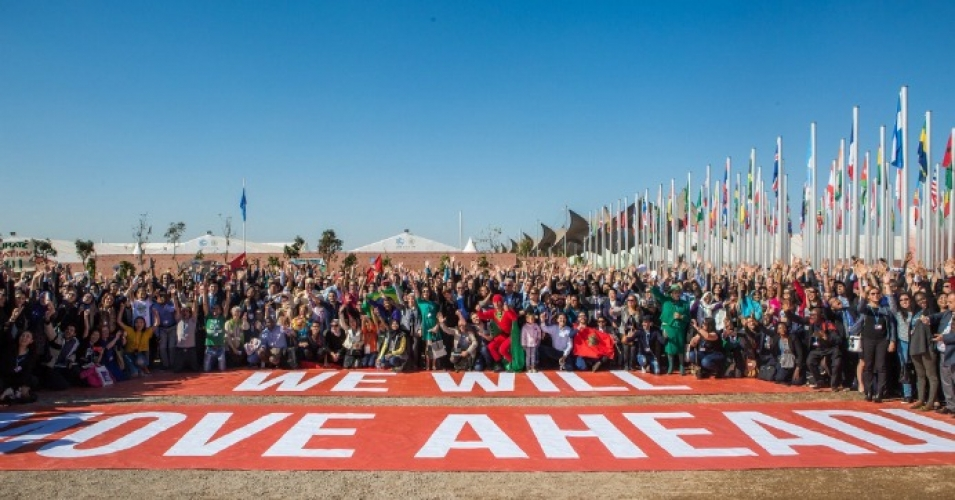 "Attendees of the United Nations climate conference in Marrakech, Morocco surround the words: ""We Will Move Ahead."" (Photo: Greenpeace)"